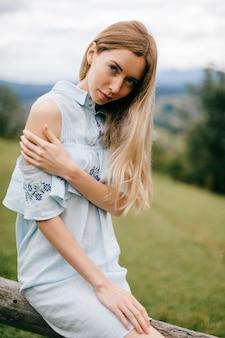 Jovem atraente loira elegante com vestido azul romântico sentada em cima da cerca de madeira no campo