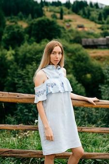 Jovem atraente loira elegante com vestido azul romântico