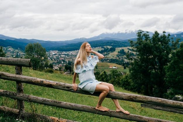 Jovem atraente loira elegante com vestido azul, sentada em cima da cerca de madeira no campo