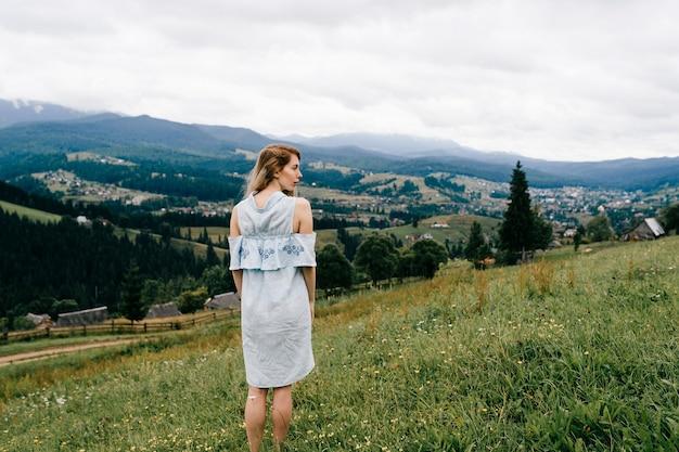 Jovem atraente loira elegante em um vestido azul posando de volta sobre uma paisagem pitoresca.