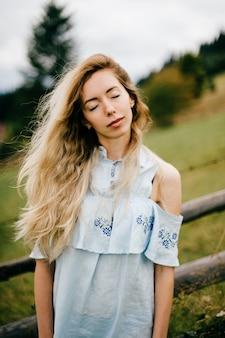 Jovem atraente loira elegante em um vestido azul posando perto de cerca na zona rural