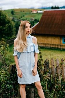 Jovem atraente loira elegante em um vestido azul posando sobre uma casa de campo no campo
