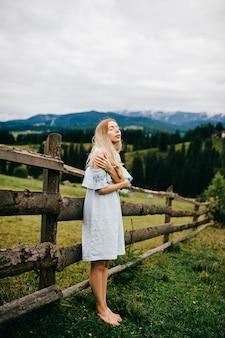 Jovem atraente loira elegante em um vestido azul romântico posando perto de cerca na zona rural
