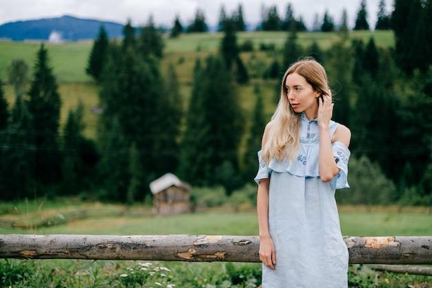 Jovem atraente loira elegante em um vestido azul romântico posando perto de uma cerca de madeira no campo