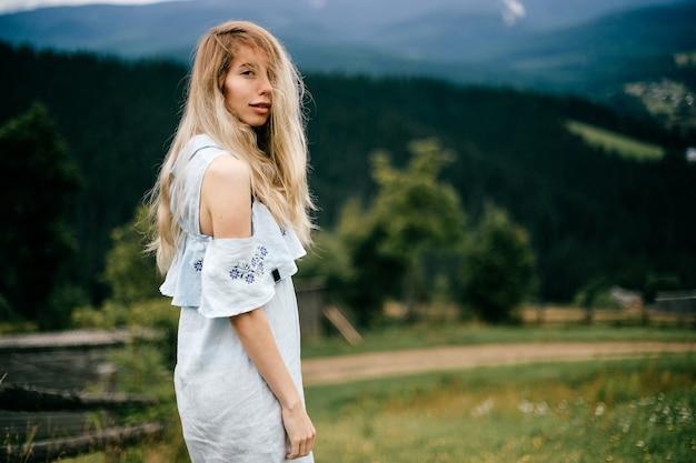 Jovem atraente loira elegante em um vestido azul romântico posando sobre uma paisagem pitoresca.