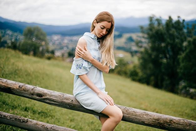 Jovem atraente loira elegante em um vestido azul romântico sentada em cima da cerca de madeira no campo