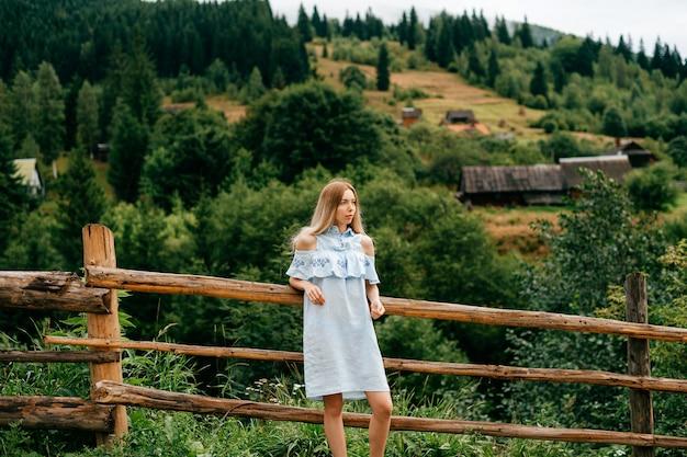 Jovem atraente loira elegante em um vestido azul se passando perto de uma cerca de madeira na zona rural.