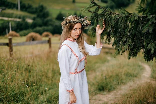 Jovem atraente loira em um vestido branco com bordado e coroa de flores na cabeça posando com um galho de pinheiro sobre a paisagem campestre