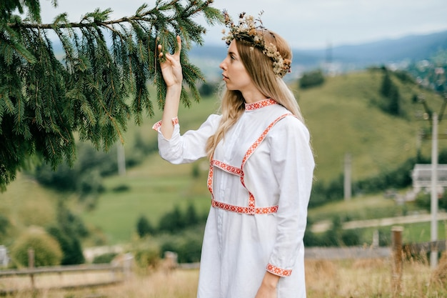 Jovem atraente loira em um vestido branco com bordado e guirlanda de flores na cabeça, posando com um galho de pinheiro sobre a paisagem campestre