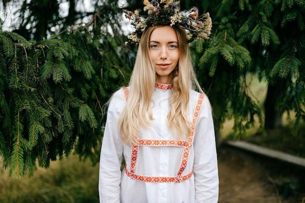 Jovem atraente loira em um vestido branco com ornamento e coroa de flores na cabeça posando sobre fundo de ramos de abeto