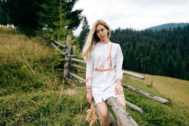 Jovem atraente loira vestido branco com ornamentos