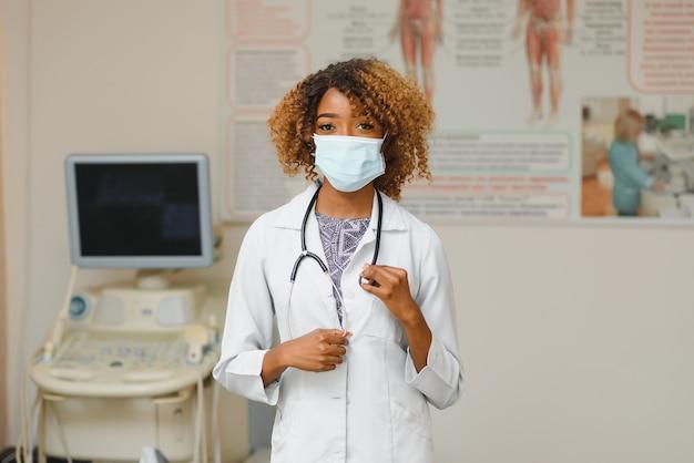 Jovem atraente médica africana com máscara facial