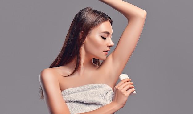Jovem atraente menina morena com cabelo solto com desodorante em bastão e aerossol antitranspirante isolado no fundo cinza. cuidado do corpo.