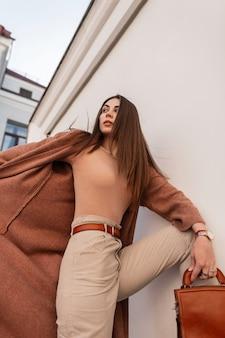 Jovem atraente moda modelo mulher elegante com cabelo castanho em um casaco da moda em calças bege com bolsa elegante de couro poses perto de parede vintage na cidade.
