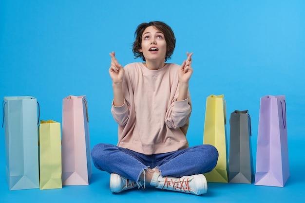Jovem atraente morena com cabelo curto e muitas sacolas de compras