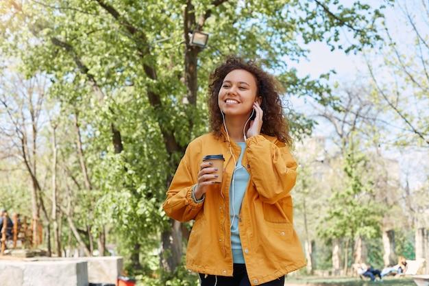 Jovem atraente morena de pele escura encaracolada, sorrindo amplamente, vestindo uma jaqueta amarela, bebendo café, segurando fones de ouvido com a mão e curtindo sua música favorita caminhando no parque em tempo bom.