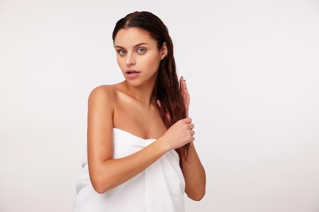 Jovem atraente morena enrolada em uma toalha de banho branca e segurando o cabelo com as mãos, posando depois do banho