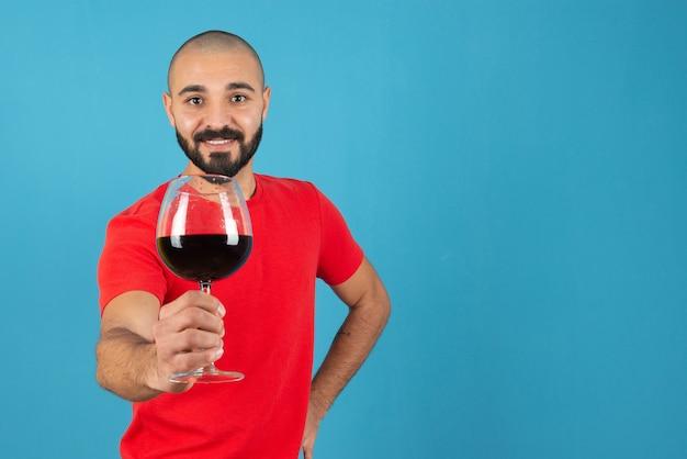 Jovem atraente mostrando uma taça de vinho tinto.