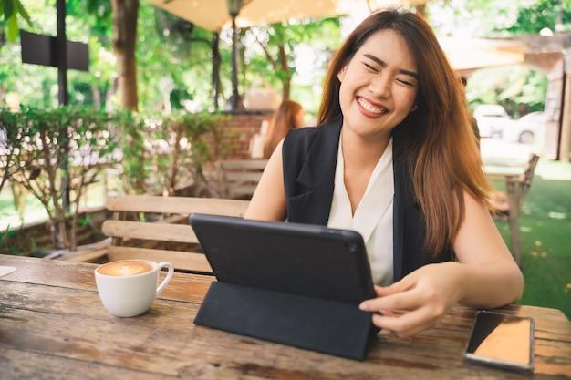 Jovem atraente mulher asiática feliz está usando tablet com cara de sorriso no café café, conteúdo on-line