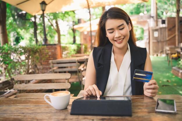 Jovem atraente mulher asiática feliz está usando tablet ou smartphone