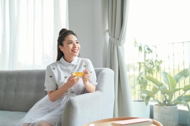 Jovem atraente mulher asiática que bebe chá