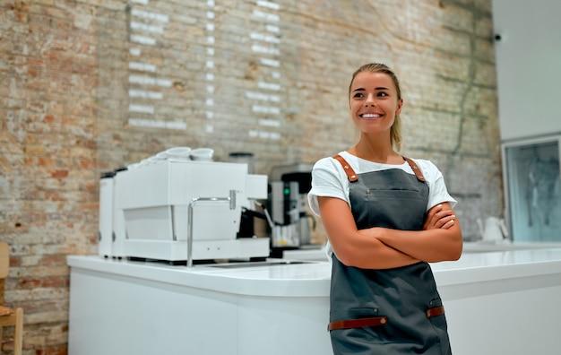 Jovem atraente mulher barista fica no balcão de uma cafeteria e sorri.