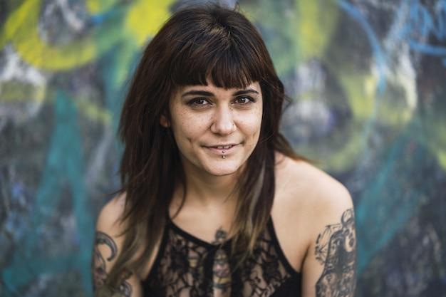 Jovem atraente mulher branca com tatuagens sentada em uma rampa de patinação