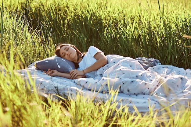 Jovem atraente mulher de cabelos escuros deitada em um travesseiro macio sob o cobertor ao ar livre, mantém os olhos fechados, dormindo ao ar livre, aproveitando o calor do verão, relaxando na natureza.