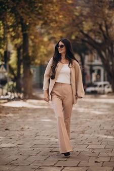 Jovem atraente mulher de negócios andando na rua