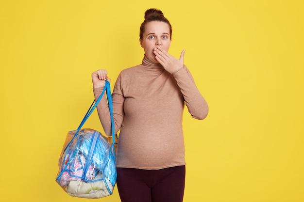 Jovem atraente mulher grávida vestindo casualmente, segurando bolsa com coisas, ficando surpresa e com medo de ir para a maternidade, cobrindo a boca com a palma da mão.