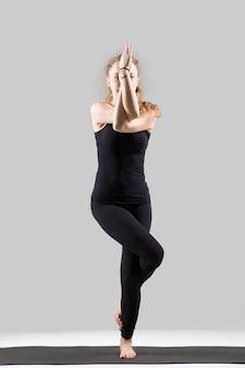 Jovem, atraente, mulher, permanente, garudasana, pose, cinzento, estúdio
