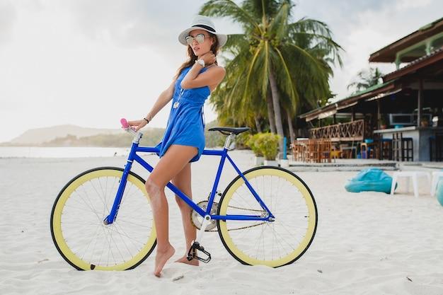 Jovem atraente mulher sorridente em vestido azul caminhando em uma praia tropical com bicicleta usando chapéu e óculos escuros