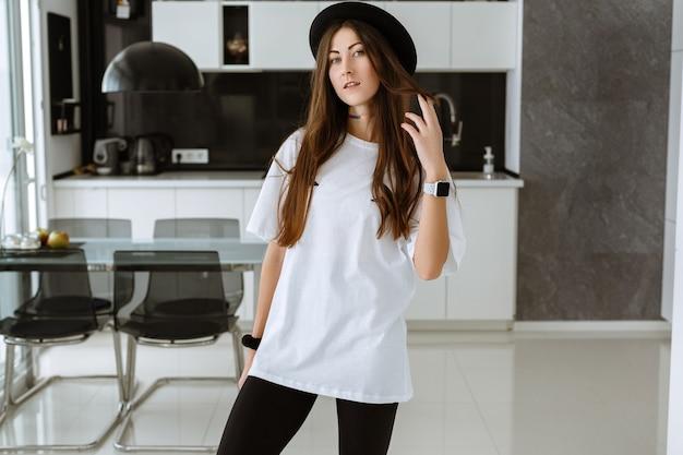 Jovem atraente mulher sorridente praticando ioga, malhando, vestindo roupas esportivas, calça preta, corpo inteiro coberto, casa. cozinha espaçosa e bem iluminada e sala de estar