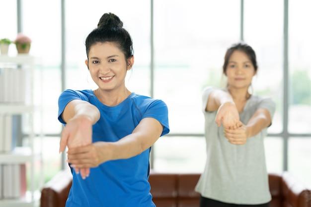 Jovem atraente mulher sorridente praticando ioga malhando, vestindo roupas esportivas, calma e relaxe, felicidade feminina.