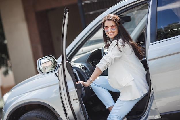 Jovem atraente no carro. mulher de negócios no automóvel. auto de condução feminina.