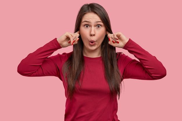Jovem atraente odeia barulho alto, tapa os ouvidos com os dedos, faz caretas de surpresa, incomodada por um som irritante, sente-se incomodada
