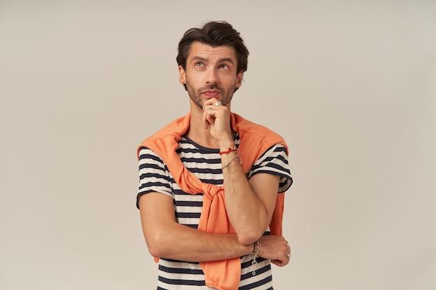 Jovem atraente pensativo com cerdas e mãos postas em uma camiseta listrada e um suéter sobre os ombros pensando e olhando para cima