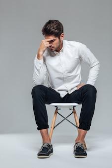 Jovem atraente pensativo e casual sentado em uma cadeira perto de uma parede cinza
