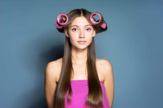 Jovem atraente posando com grandes rolos de cabelo rosa na cabeça