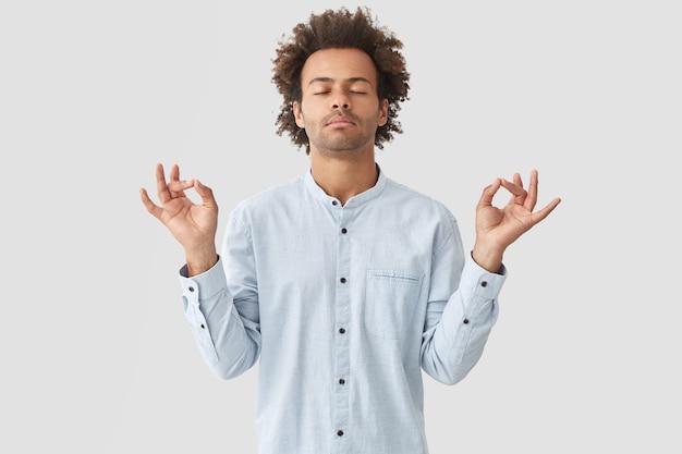 Jovem atraente pratica ioga, sente-se relaxado e calmo, mostra o sinal de mudra com as duas mãos, fecha os olhos tentando se concentrar em algo, posa sozinho contra uma parede branca