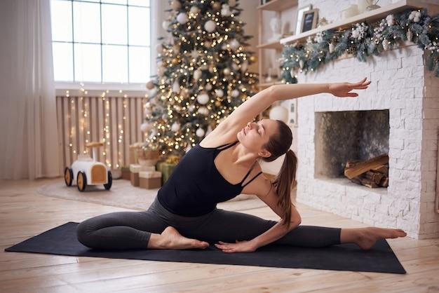 Jovem atraente praticando ioga em casa moderna