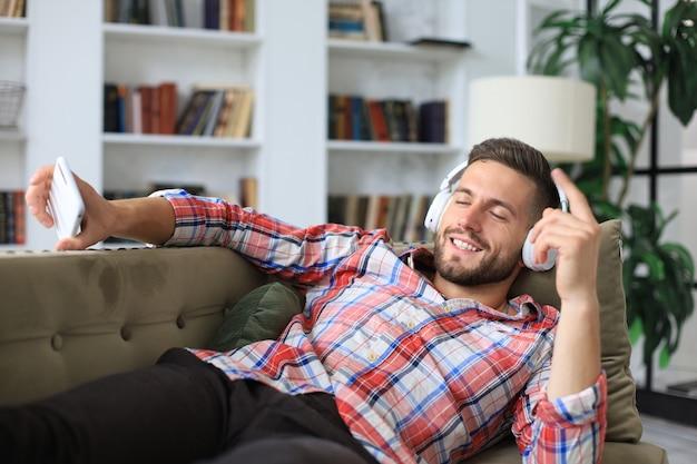 Jovem atraente relaxando em um sofá em casa, ouvindo música e tocando no smartphone.