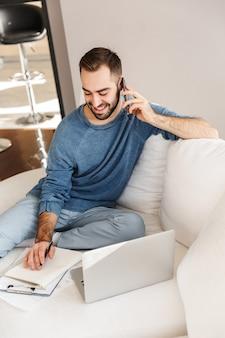 Jovem atraente relaxando em um sofá em casa, trabalhando em um laptop, falando no celular