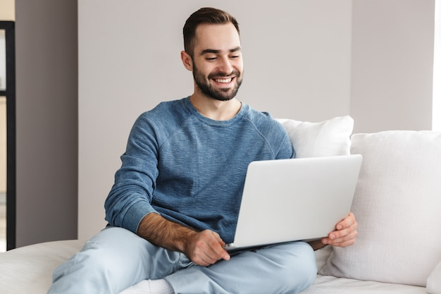 Jovem atraente relaxando em um sofá em casa, trabalhando em um laptop