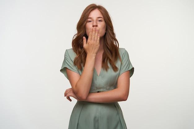 Jovem atraente ruiva com penteado beijando a palma da mão e olhando, de pé, usando um vestido vintage em cor pastel