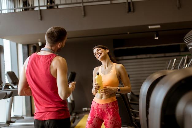 Jovem atraente, segurando garrafas de água e sorrindo em pé com personal trainer no ginásio