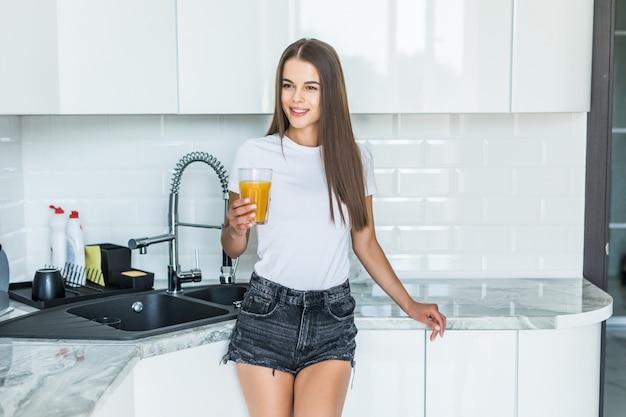 Jovem atraente, segurando um copo de suco de laranja em pé na cozinha