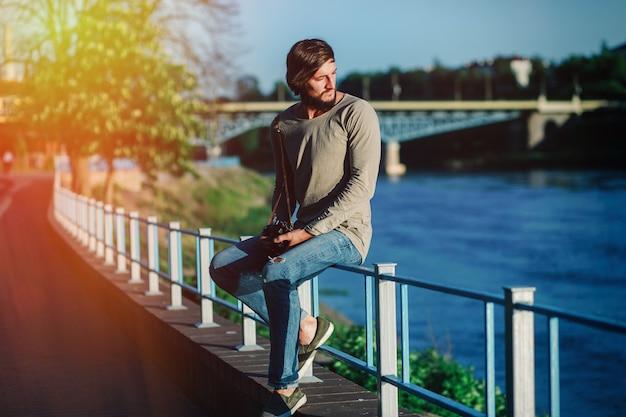 Jovem atraente sentado no parapeito na margem do rio e desviando o olhar