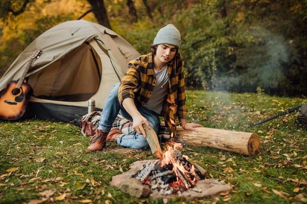 Jovem atraente sentado no tronco jogando lenha perto de uma barraca de turista na floresta