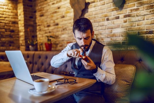 Jovem atraente sofisticado empresário barbudo de terno sentado no café e iluminando o tubo com tabaco. na mesa estão o laptop e o café.